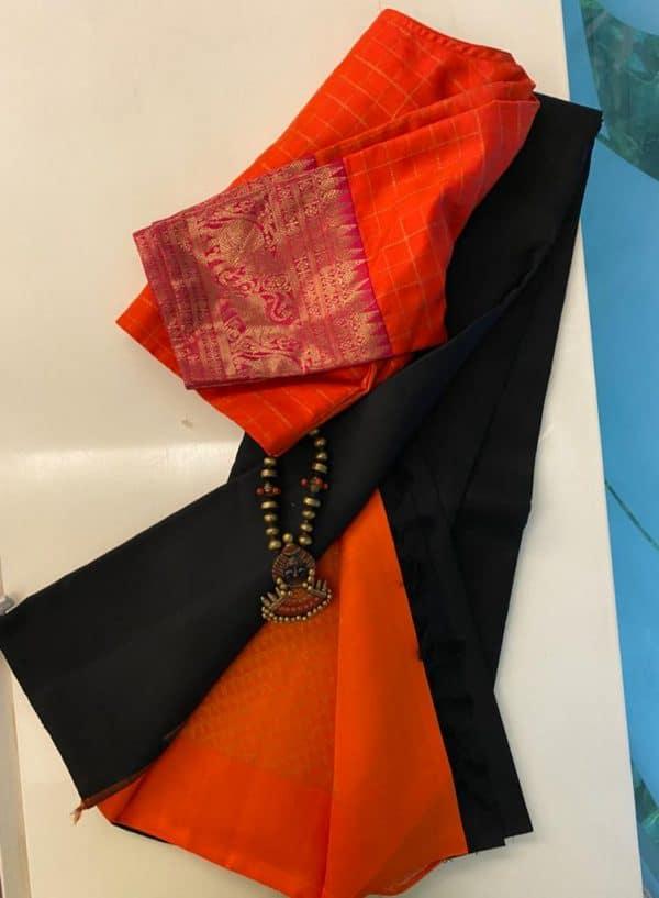 Black kanchipuram silk saree with orange pallu and blouse