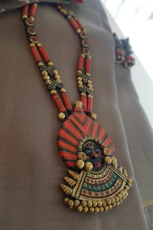 Orange neck piece with faces pendant