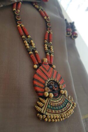 Orange neck piece with faces pendant
