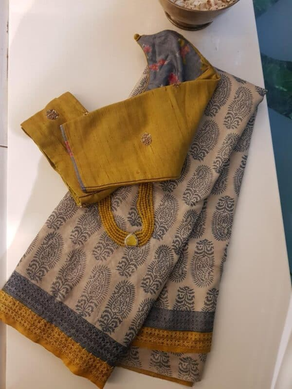 beige tussar saree with paisley and kutchwork border